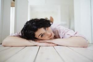 Brunette young woman lying on floor