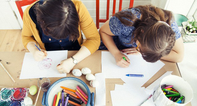 Overhead view of teenage girl and older sister painting easter eggs